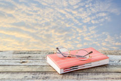 Notebook and eyeglasses on wooden background Stock Photo