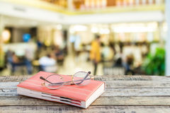 Notebook and eyeglasses on wooden table with blur background Royalty Free Stock Images