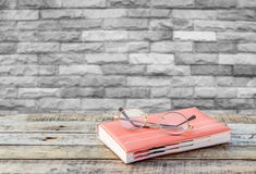 Notebook and eyeglasses on wooden table with blurred brick wall Royalty Free Stock Image