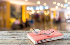 Notebook and eyeglasses on wooden table with blurred hotel lobby Royalty Free Stock Photo