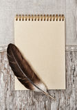 Notebook, feather  and linen fabric on the old wood Stock Photos