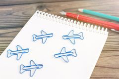 Notebook, figures in the form of airplanes, pen, pencil. On a wooden background. journey. air Transport Royalty Free Stock Images