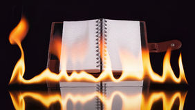 Notebook in fire flame Stock Photos