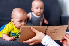 Notebook in the foreground. In the background are twins, a boy and a girl of 7 months. Maternity. Selective focus. Notebook in the foreground. In the background stock images