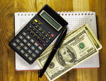 Notebook with fountain pen, banknotes, calculator on a wooden ta Stock Photos