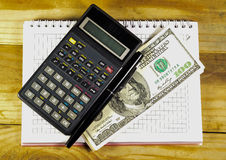 Notebook with fountain pen, banknotes, calculator on a wooden ta. Notebook with fountain pen, banknotes and calculator on a wooden table Stock Photo