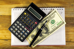 Notebook with fountain pen, banknotes, calculator on a wooden ta. Notebook with fountain pen, banknotes and calculator on a wooden table Royalty Free Stock Photo