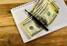 Notebook with fountain pen and banknotes on the wooden table Royalty Free Stock Image