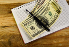 Notebook with fountain pen and banknotes on the wooden table Stock Photos