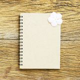 Notebook and Frangipani flower on wooden table Royalty Free Stock Photography