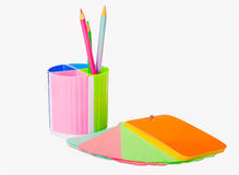 Notebook and glass of crayons. Notebook of colored paper and plastic cup with crayons on white background Stock Photos