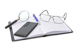 Notebook, glasses, cell phone and magnifying glass Royalty Free Stock Image