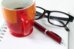 Notebook glasses coffee cup Stock Image