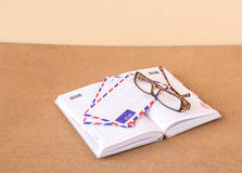 Notebook, glasses and envelope on a wood background Stock Photos
