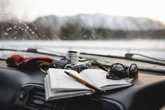 Notebook, glasses and film camera on the dashboard. In the car. Closeup shot, mountains on the background stock photography