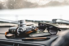 Notebook, glasses and film camera on the dashboard. In the car. Closeup shot royalty free stock photography