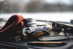 Notebook, glasses and film camera on the dashboard. In the car. Closeup shot stock images