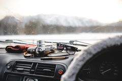 Notebook, glasses and film camera on the dashboard. View from the driver seat. Notebook, glasses and film camera on the dashboard in the car. Closeup shot royalty free stock photos