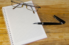 Notebook with glasses and fountain pen on wooden desk Stock Photography