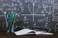 Notebook, glasses and a glass with pencils on chalkboard background with formulas. Teacher's day concept and back to school