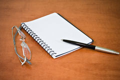 Notebook, glasses and pen Stock Photos