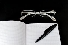Notebook, glasses and pen and on a black background Royalty Free Stock Photography