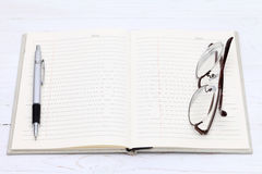 Notebook and glasses. Pen on the white wooden table Stock Photo