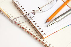 Notebook glasses pen and yellow pencil on white ba. The notebook glasses pen and yellow pencil on white background Royalty Free Stock Images