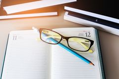 Notebook, glasses, pencil and books are on the table. Desk of a businessman or entrepreneur. royalty free stock photos