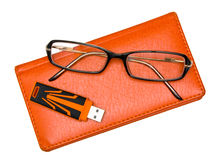 Notebook, glasses and pendrive isolated on white. Orange closed notebook, glasses and pendrive isolated on white background Royalty Free Stock Images