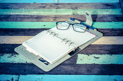 A notebook and glasses Stock Photography