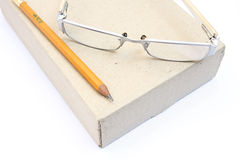 Notebook glasses and yellow pencil on box Royalty Free Stock Photography