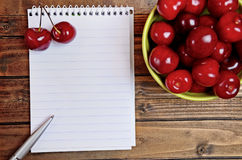 Notebook and green bowl with cherry Royalty Free Stock Photos