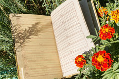 Notebook on green grass with flowers Royalty Free Stock Photo
