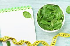 Notebook, green spinach leaves and tape measure on wooden table top view. Diet and healthy food. Notebook, green spinach leaves and tape measure on wooden table royalty free stock photography