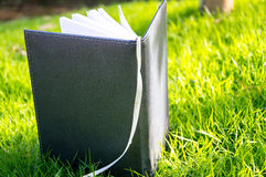 Notebook is on greensward Royalty Free Stock Images