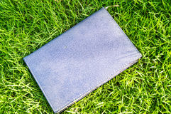 A notebook is on greensward. Royalty Free Stock Image