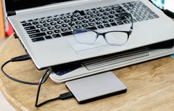Notebook grey modern black keyboard with hdd grey and spectacles Royalty Free Stock Photo