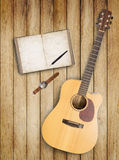 Notebook and guitar on wood table for text and background Stock Photos