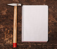 Notebook and hammer on the wooden table Royalty Free Stock Images