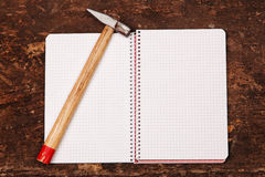 Notebook and hammer on the wooden table. Notebook and hammer on the old wooden table Royalty Free Stock Photo