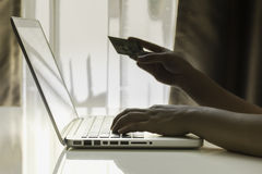 Notebook Hand Card. Woman used a notebook and read credit card number,Close up with her hand on keyboard Stock Photo