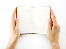 Notebook in hand. Woman hand carrying an empty book isolated on white background Royalty Free Stock Photo