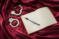 Notebook and handcuffs Royalty Free Stock Photo