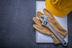 Notebook hard hat adjustable wrench protective gloves constructi Stock Image