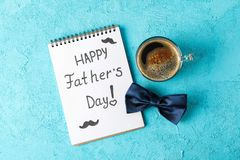 Notebook with inscription happy fathers day, blue bow tie and cup of coffee on color background, space for text. And top view stock image