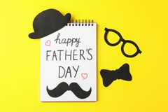 Notebook with inscription happy fathers day, decorative bow tie, glasses, mustache and hat on color background. Space for text royalty free stock image