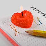 Notebook with the inscription and red candle closeup Stock Photography