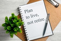 Notebook with Inspirational Quote. Plan to Live not Retire. Plan to live not retire. Inspirational quote on notebook with pen, clipboard and potted plant Stock Image
