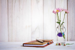 Notebook or journal with pen of flowers. Notebook or journal with pen of flowers arranged on a neutral white painted desk Royalty Free Stock Image